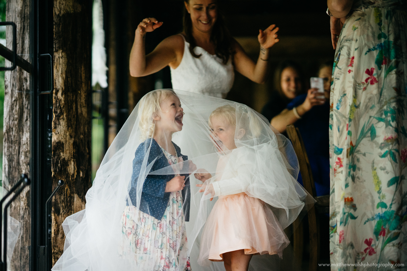 Kids having lots of fun under the wedding dress