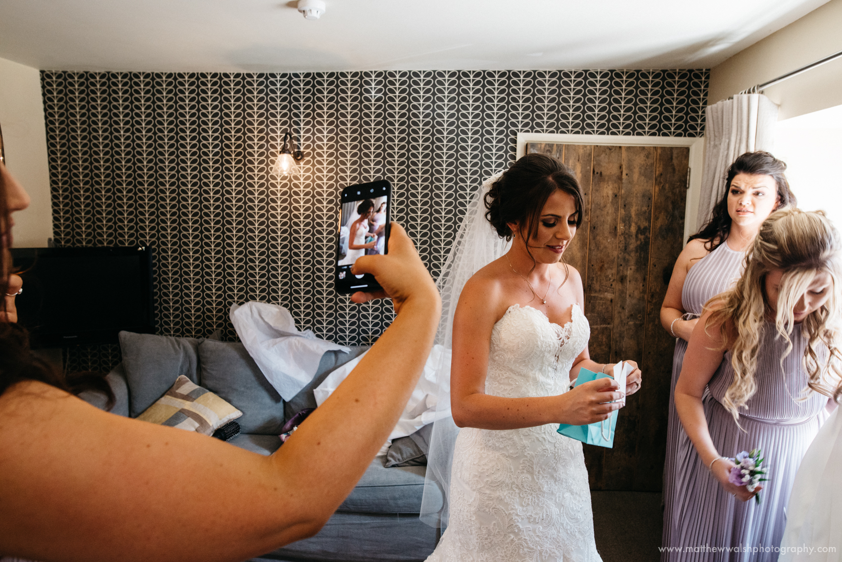 A bridesmaid takes a photo of the bride