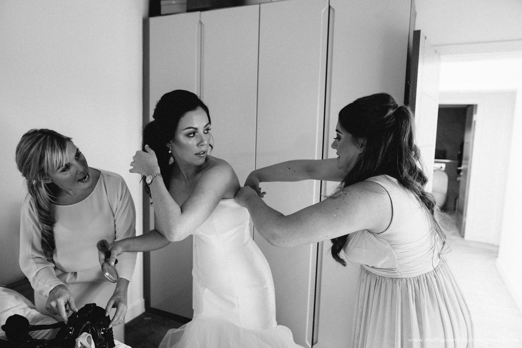Bride has help putting her dress on