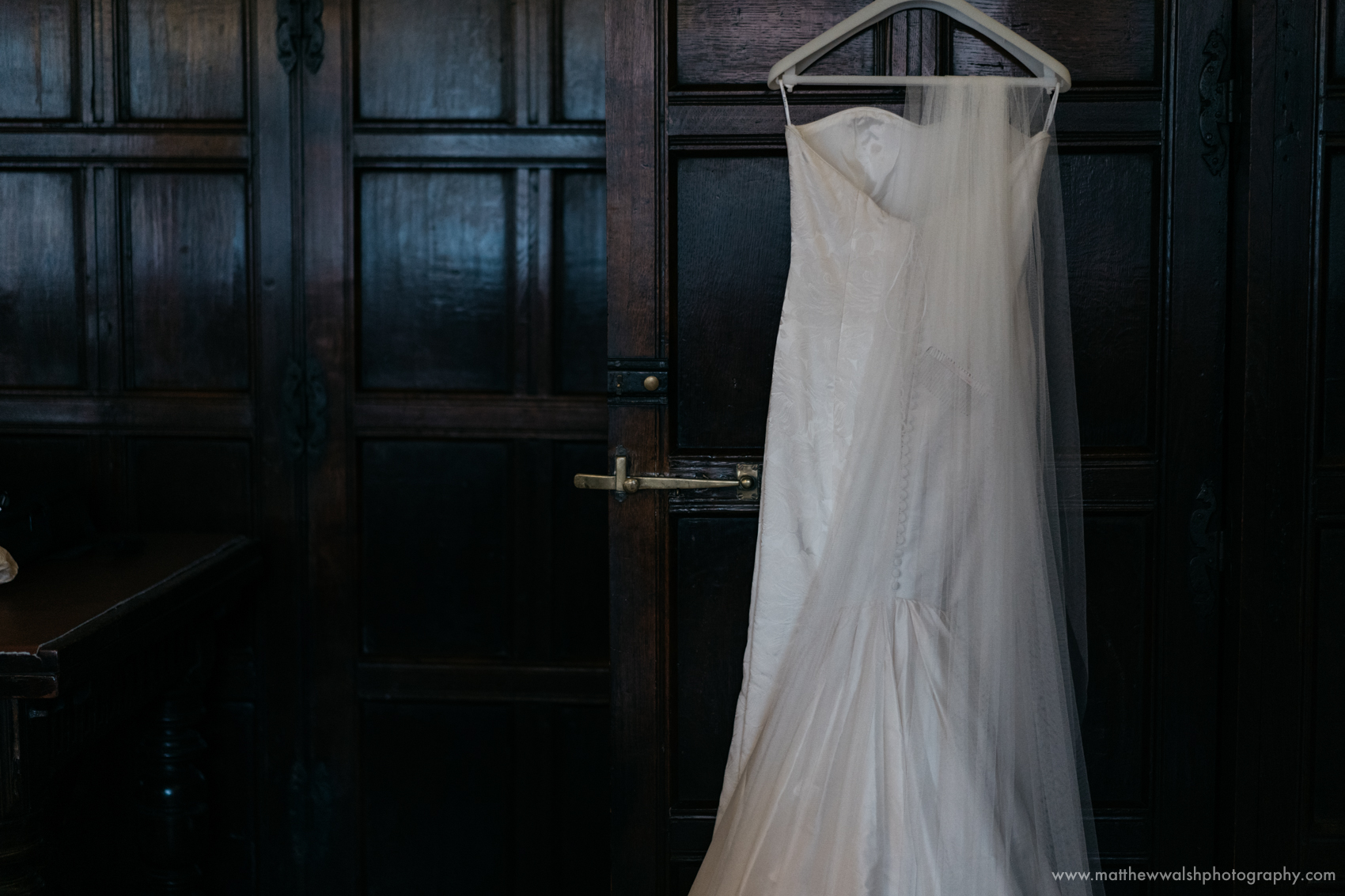 The wedding dress hanging from the door with a backdrop of natural wood panelled walls