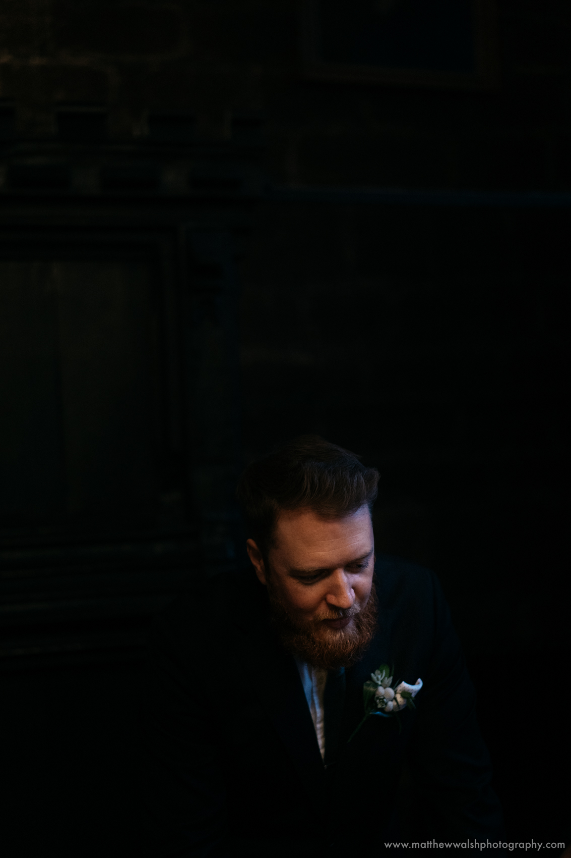 The groom making his final preparations in the dark light of the wedding venue