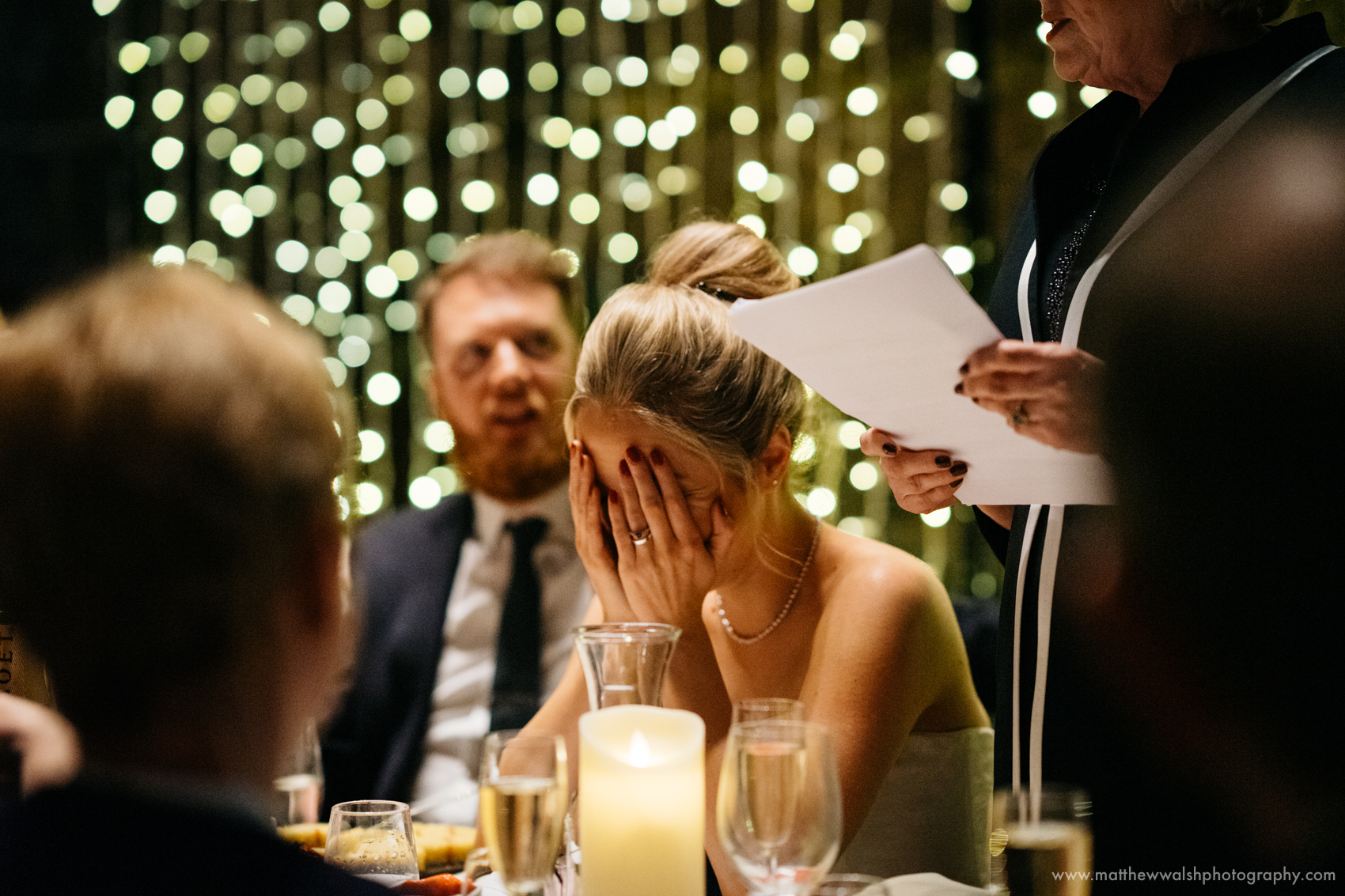An embarrassed bride holds her head as the mother of the bride makes a speech