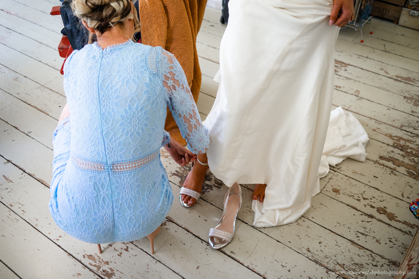 Sister of the bride helping the bride with her shoes