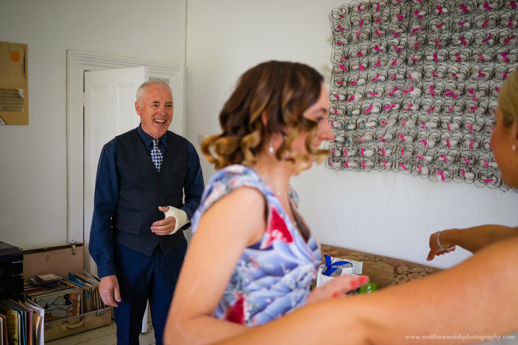 The father of the bride sees his daughter in her wedding dress for the first time