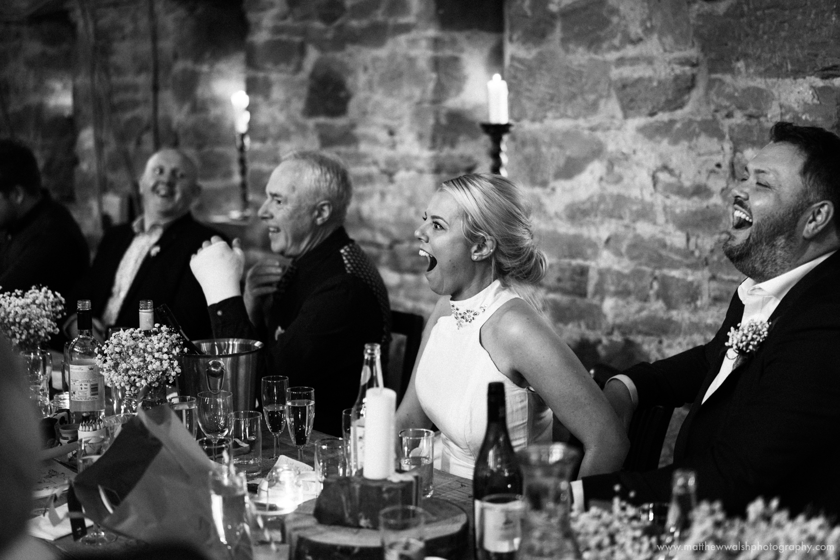 The bride and groom laughing at the poem