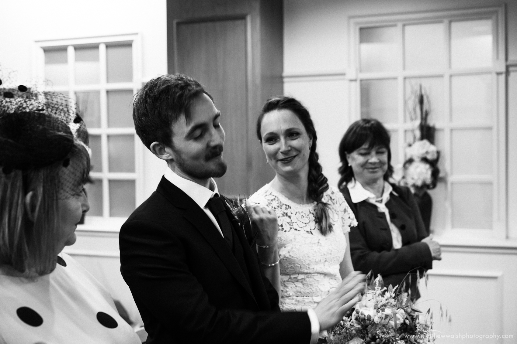A black and white photograph of the bride and groom sharing their wedding vows
