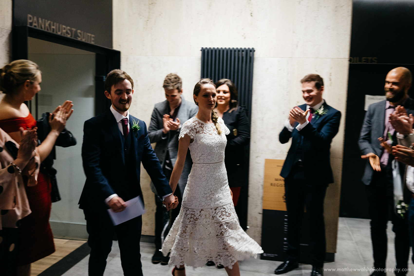 The bride and groom walk out of the ceremony venue to be met by their close friends and family