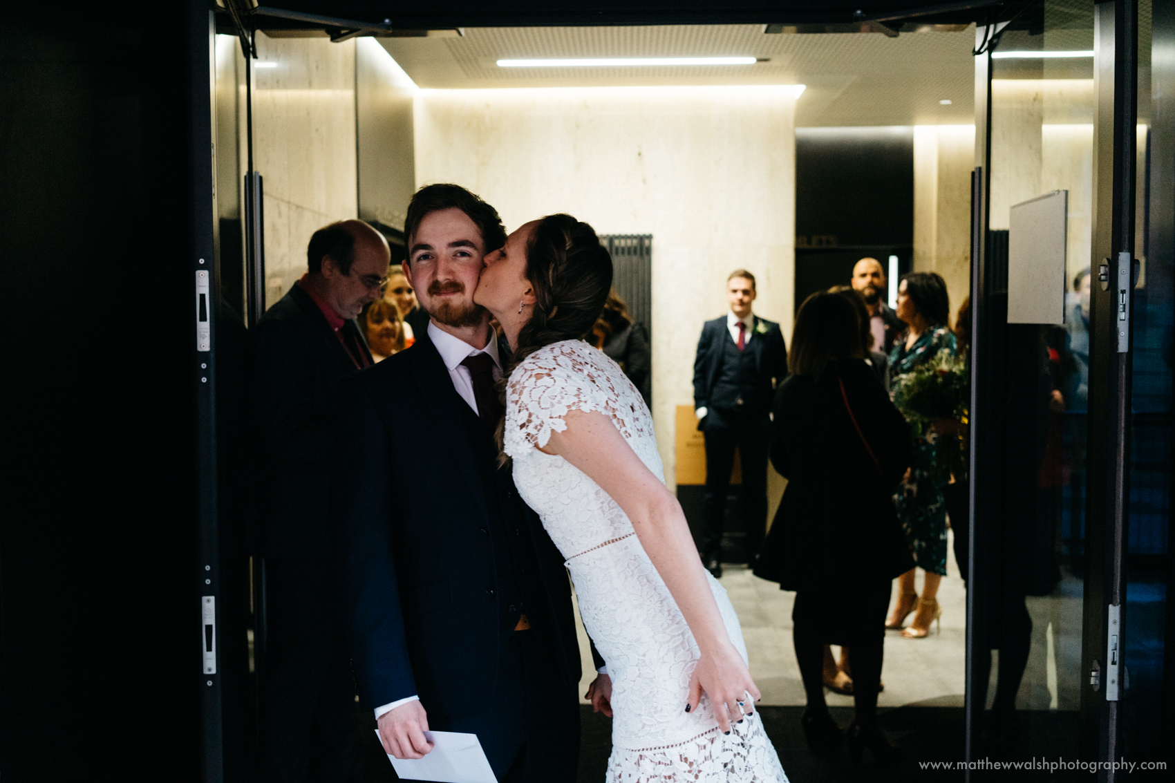 The bride gives her husband a quick kiss before the camera