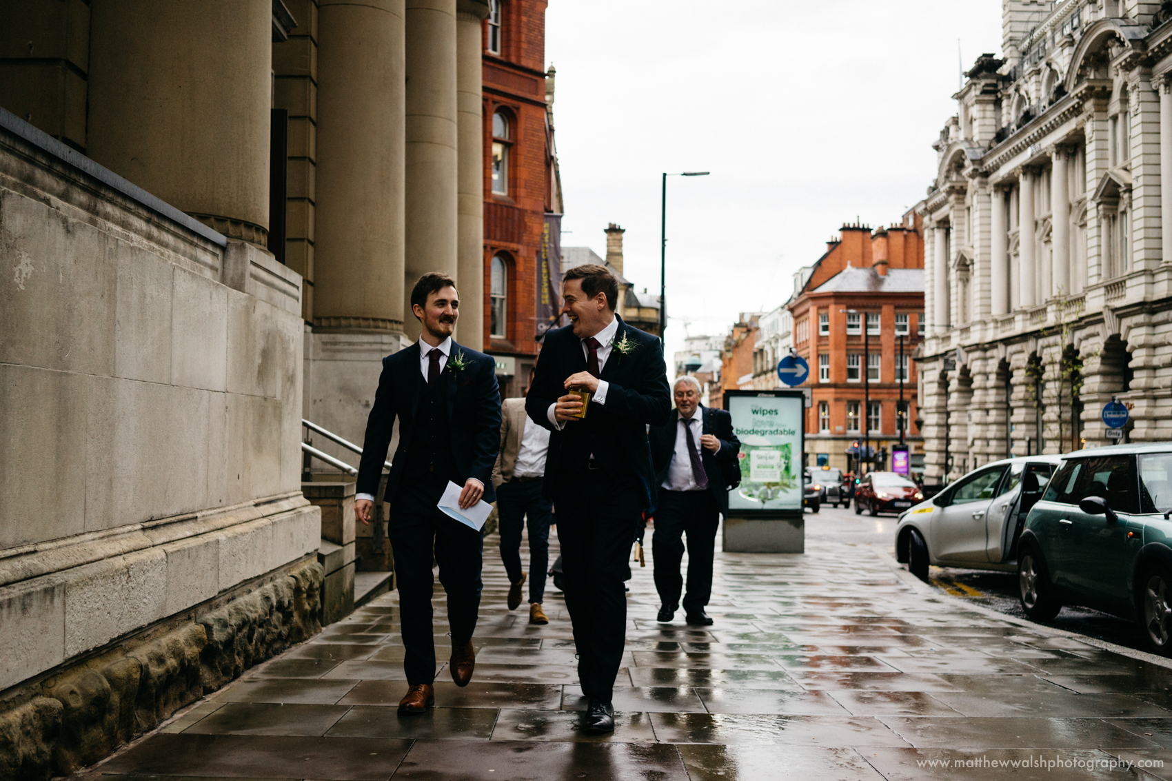The best man and groom share a wee tipple from a hip flask on their walk from the ceremony  to the bar and restaurant