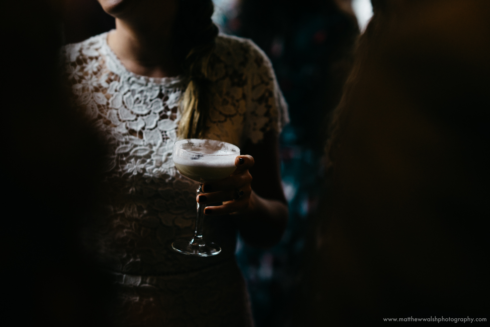 A slither of light catches the brides drink and dress, not a moment to be missed