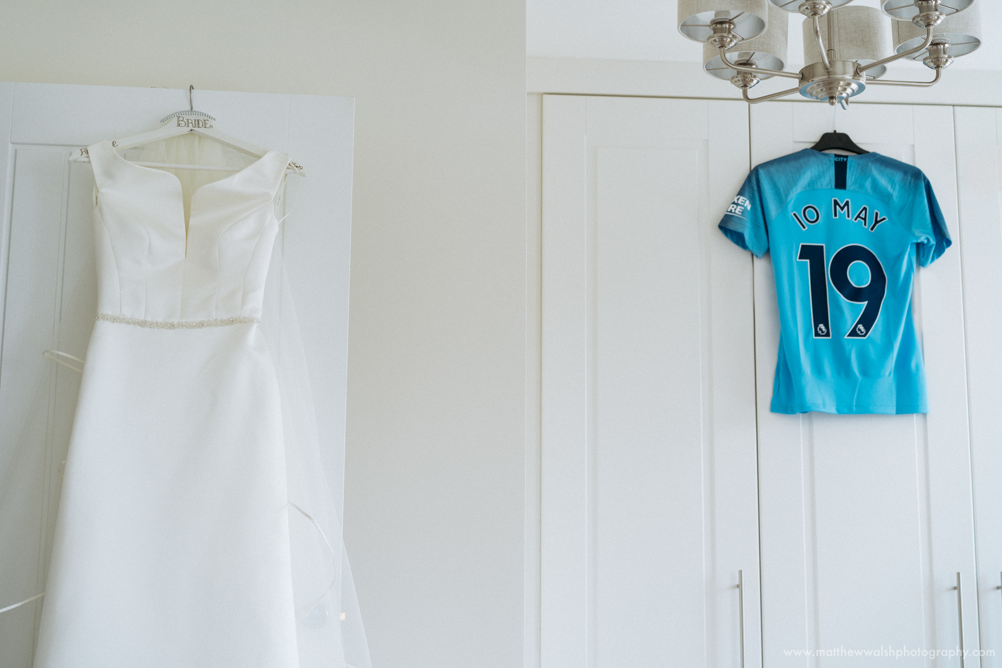 The wedding dress hanging bu a Manchester City football shirt with the wedding date on, the bride being a big football fan