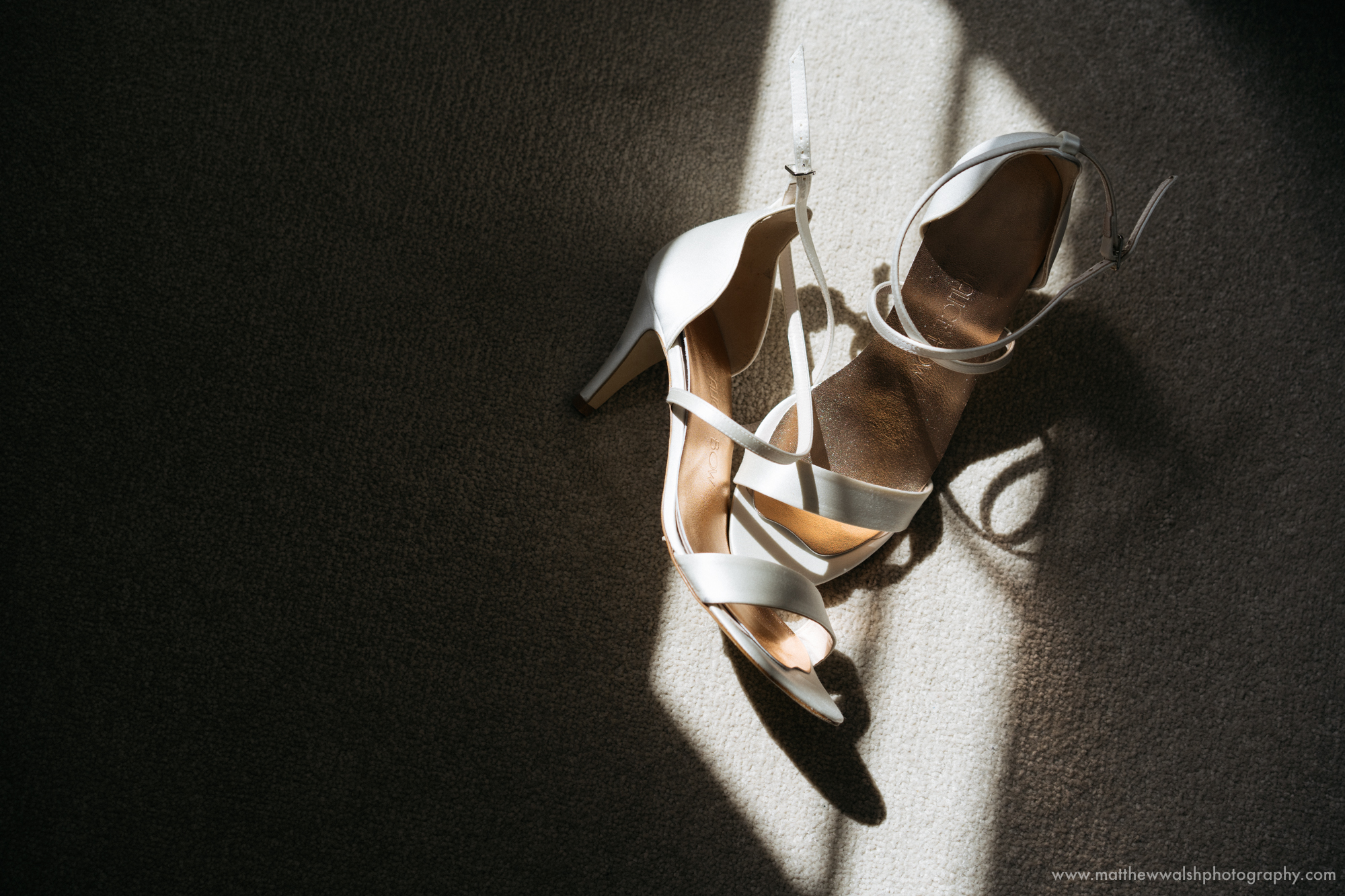 The brides shoes sitting in a pocket of natural sunlight