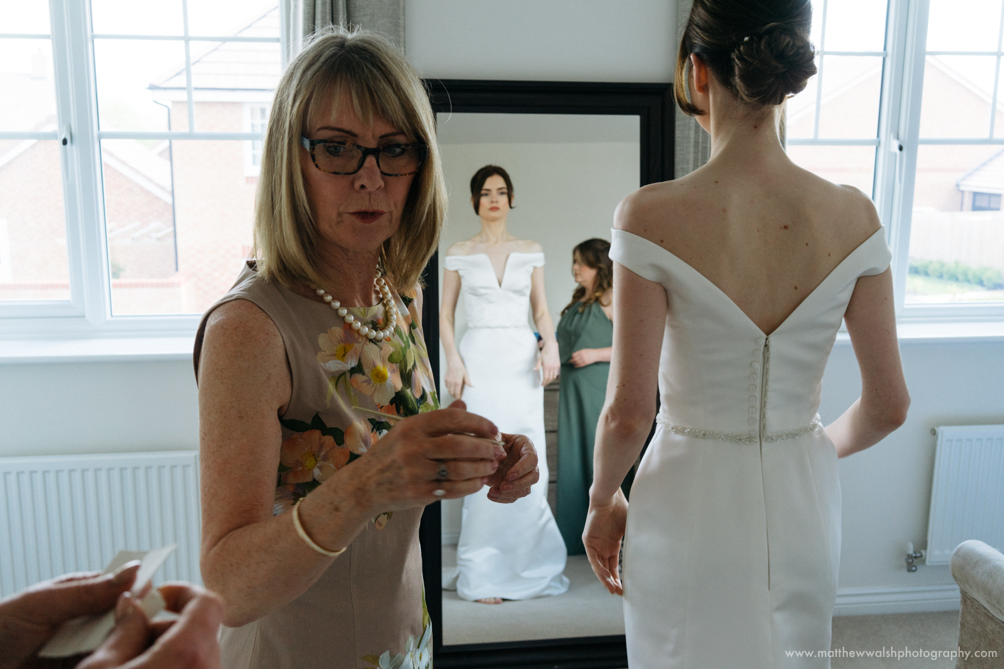 The mother of the bride helps her daughter to put her dress on in keeping with tradition
