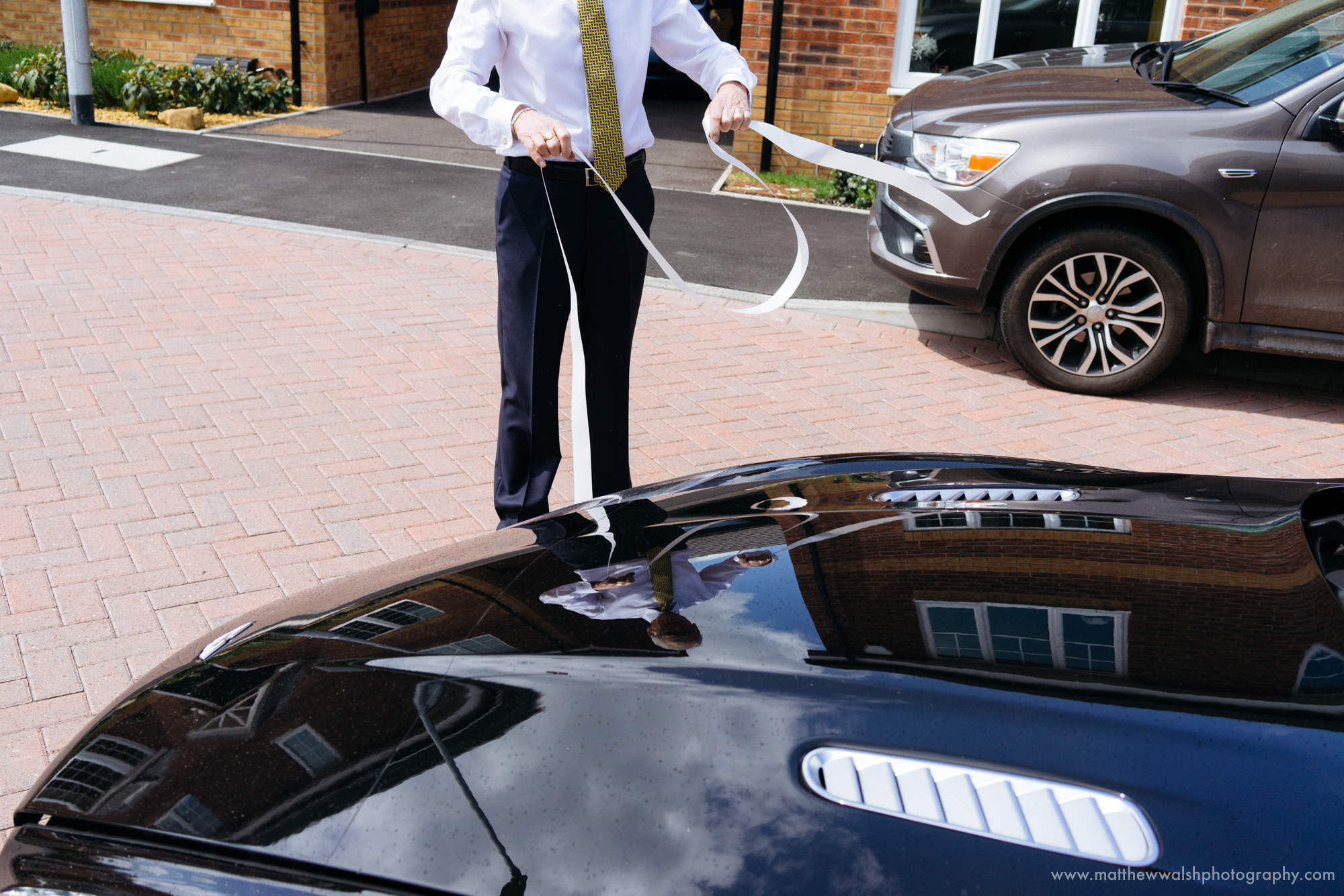 The father of the bride struggling with the ribbon that he is trying to put on the wedding car