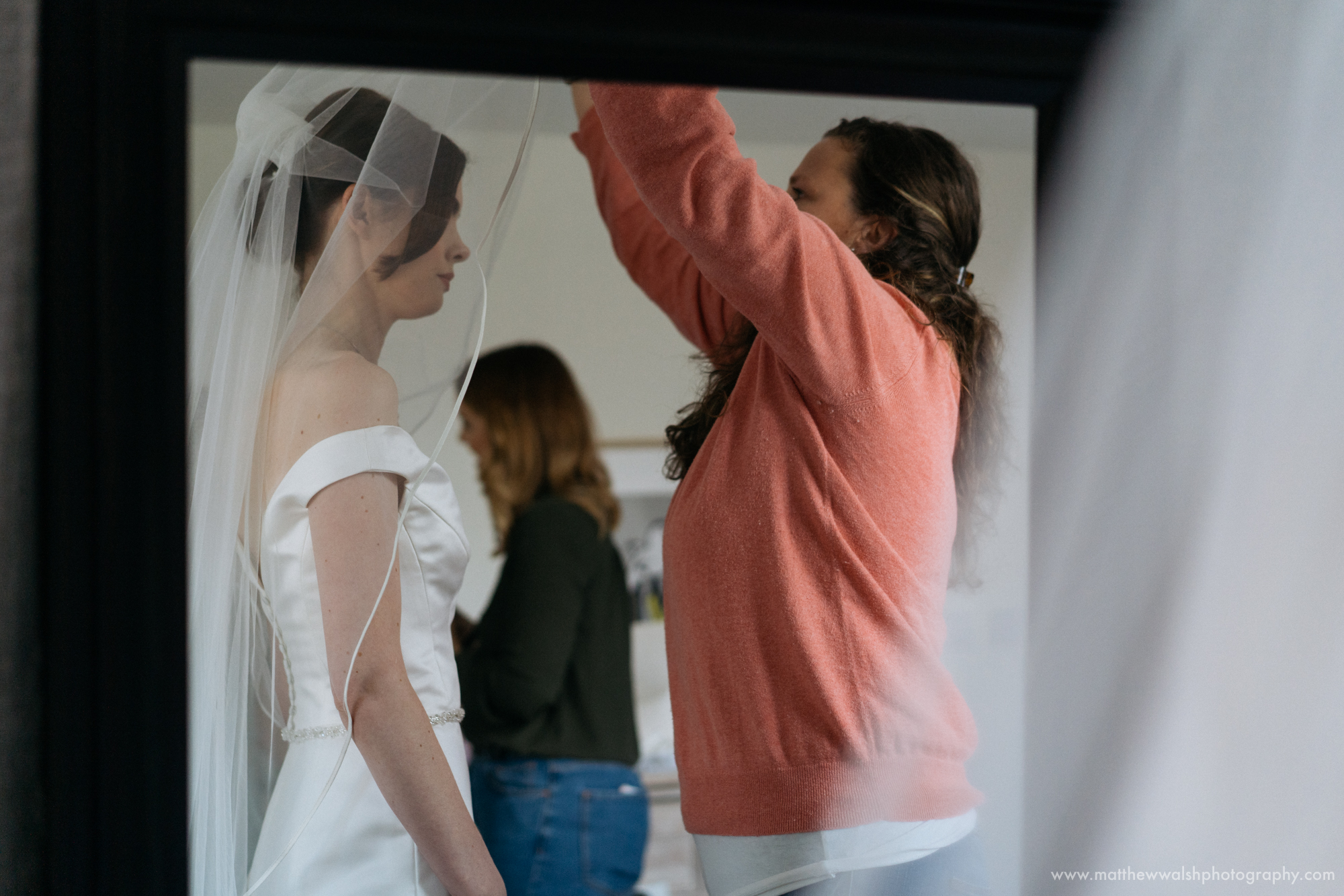 The hair stylist helping the bride with her veil