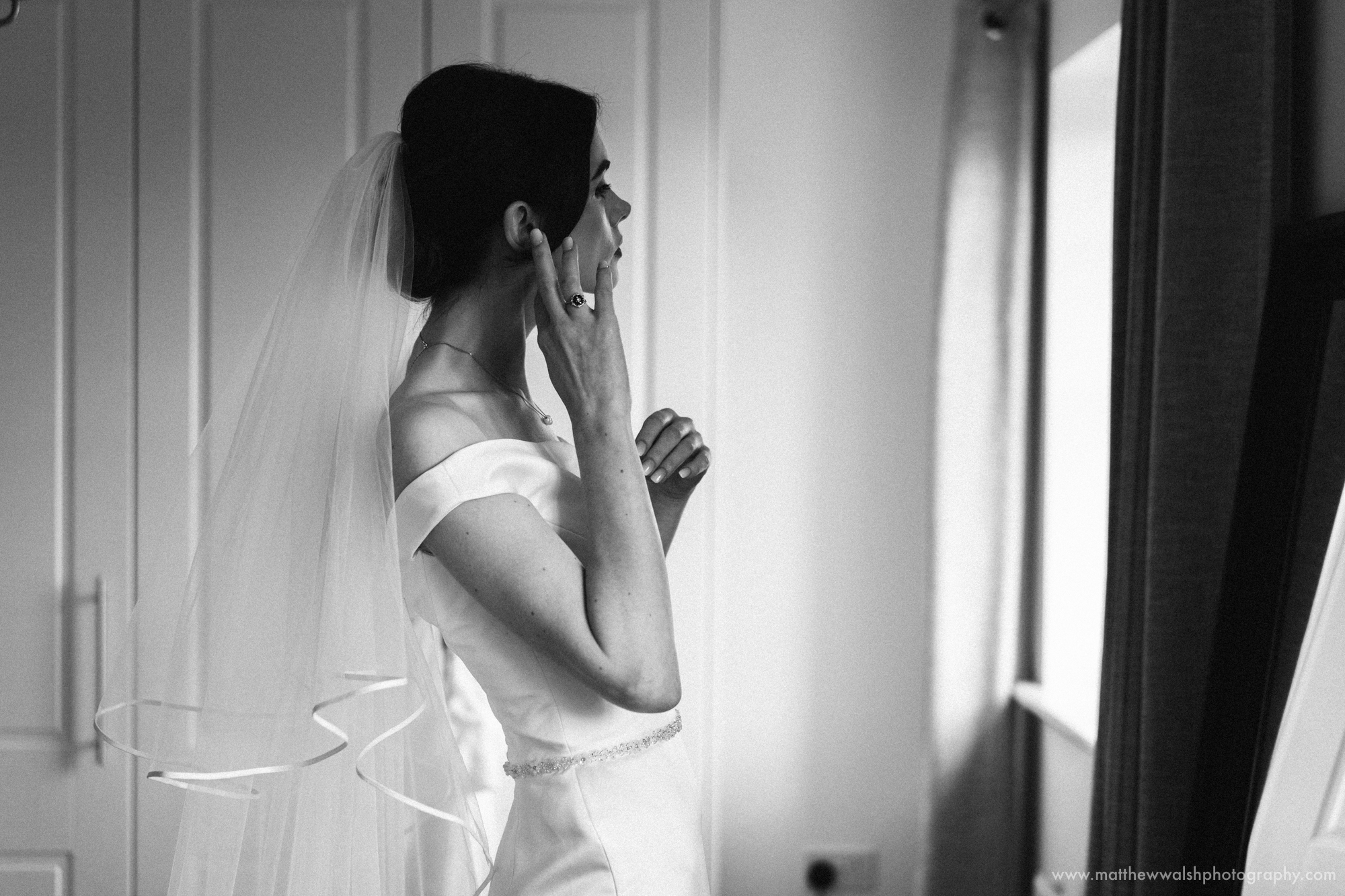 A simple fuss free image of the bride putting her earings in