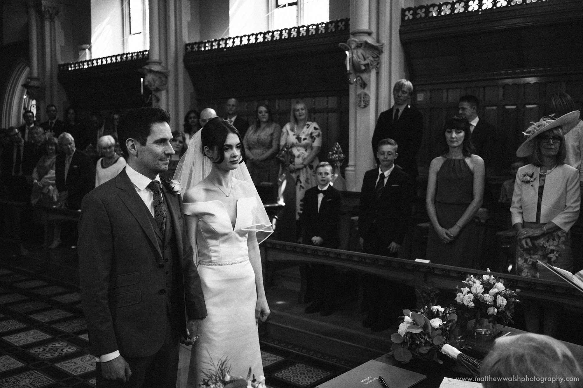 an emotional black and white image of the happy couple during the ceremony