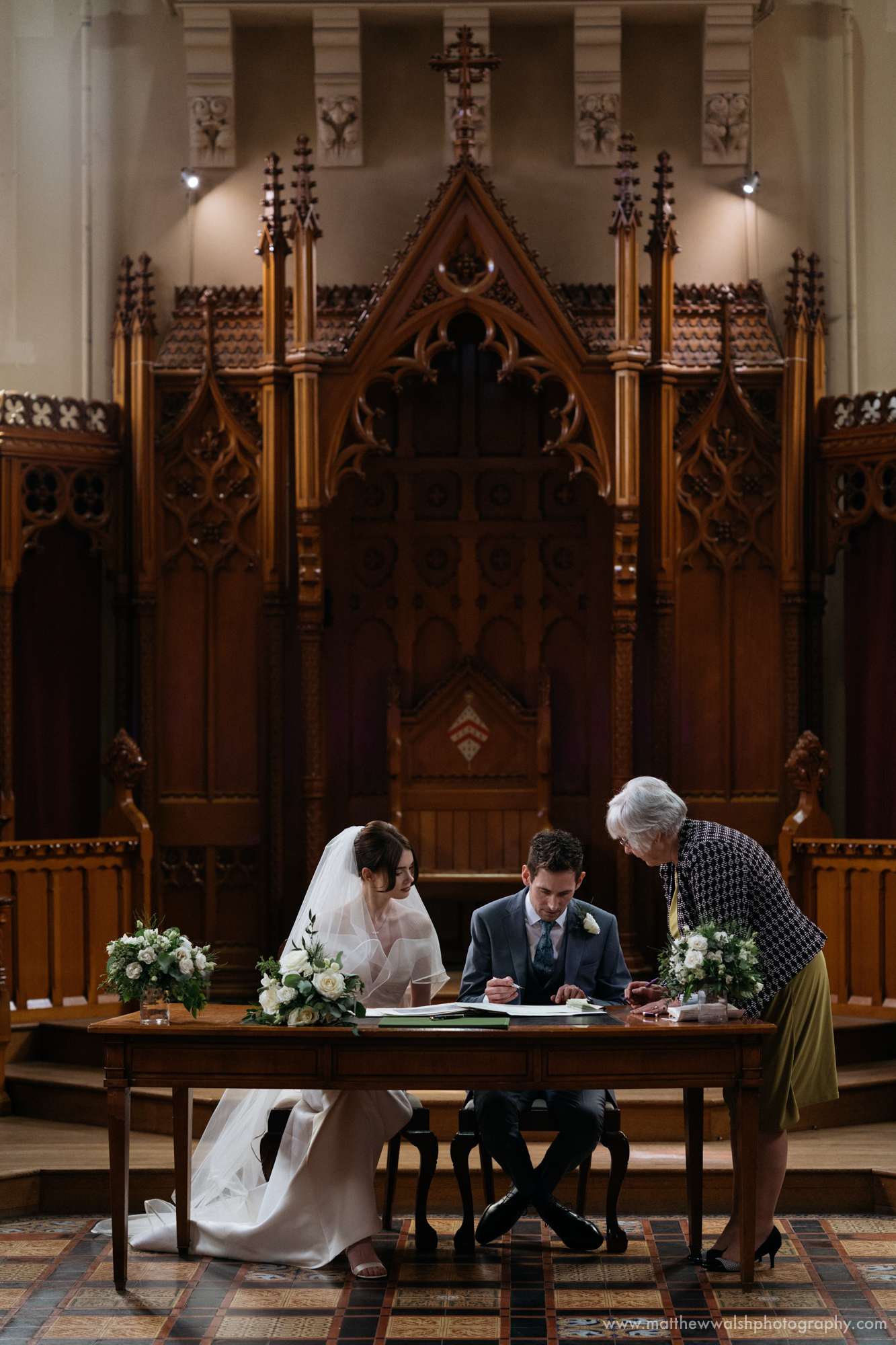Signing the wedding register in the hall chapel at Stanbrook Abbey