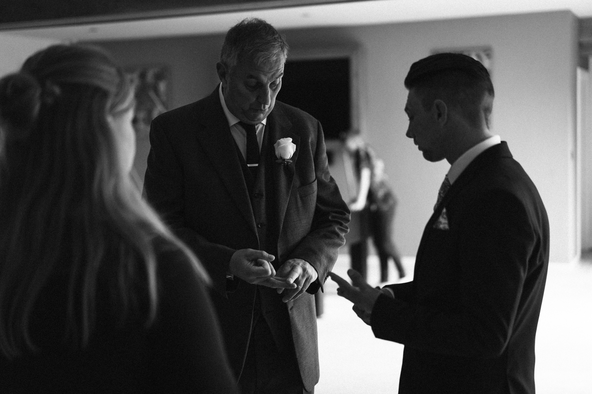 The groom and his father work out who needs button hole flowers