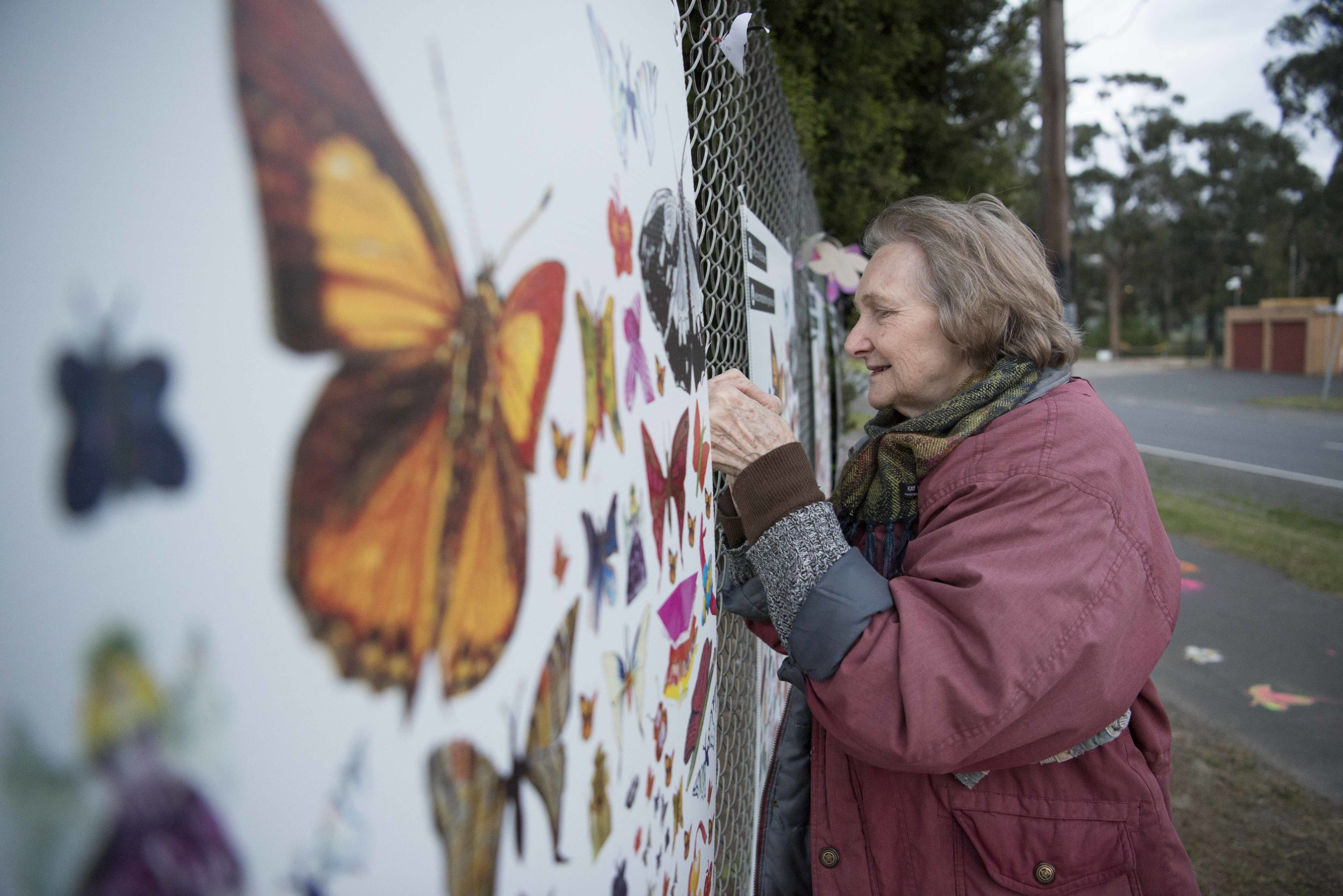 Local artist turned art ninja Janet ties one of her hand-painted butterflies to the fence.