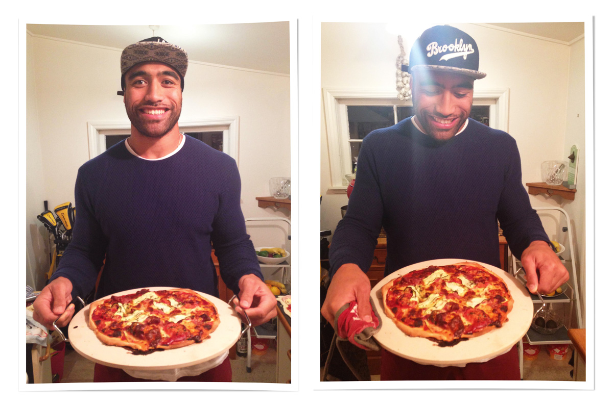 All Black Victor Vito, in a black jumper and baseball cap, holds out the home made pizza he has made