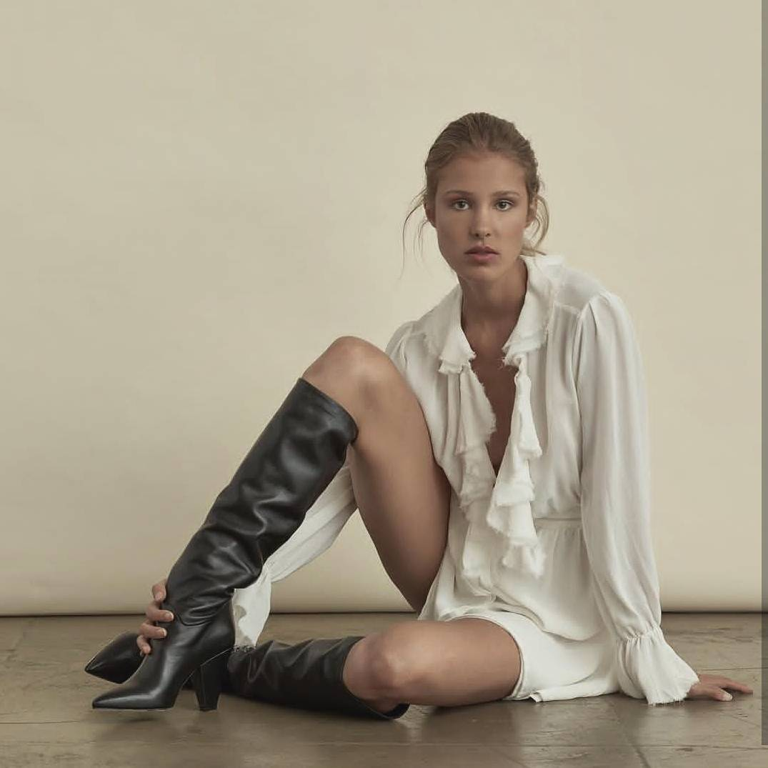 Claudia Liberova sits on the floor for the camera in a white blouse and knee high black boots