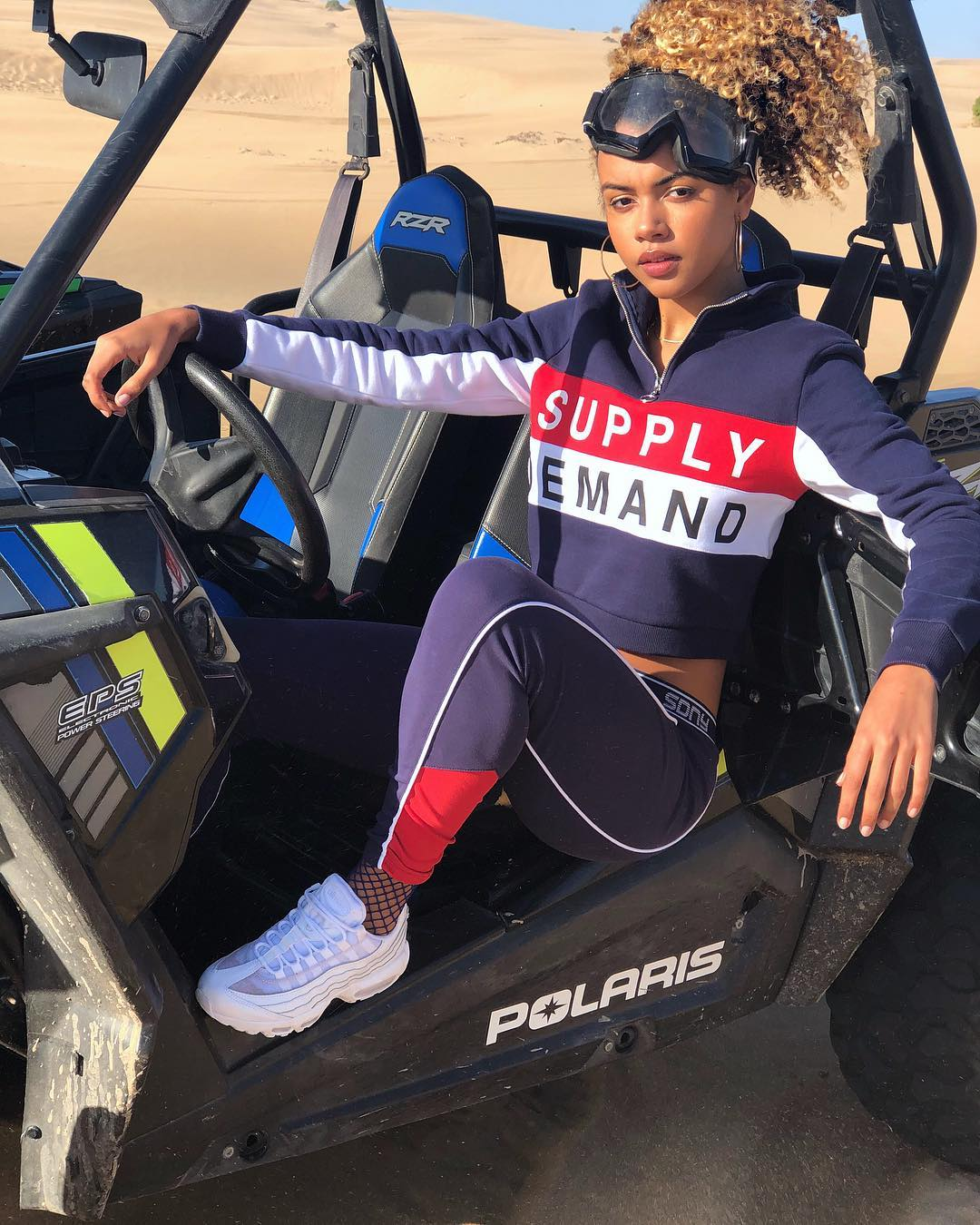 Ocean Lewis, in Supply & Demand clothing, poses in a dune buggy in the desert