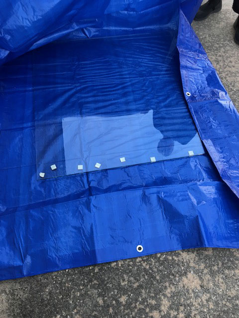 Laying the large sheet of tempered glass on a tarp.