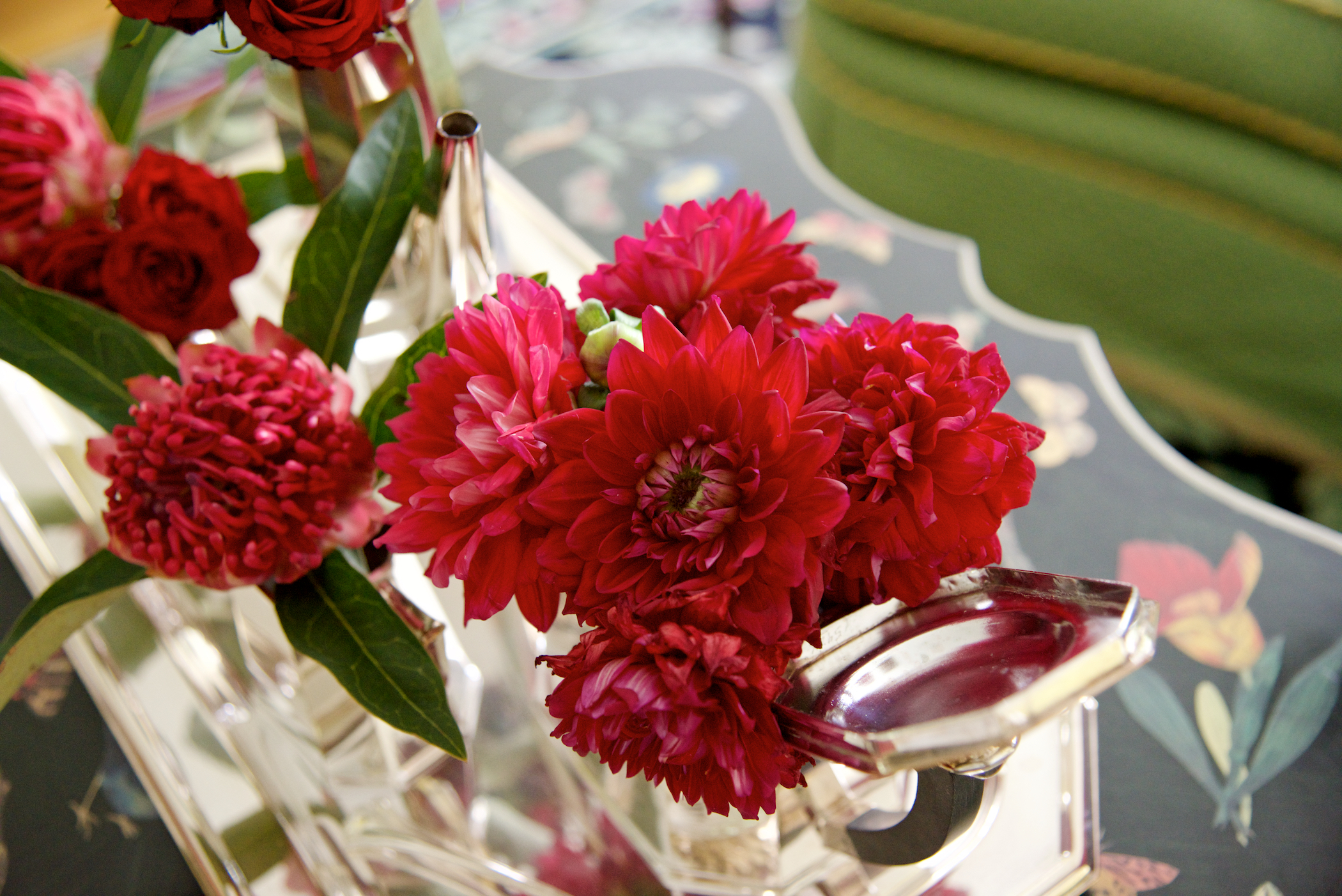 Red dahlias and roses adorn this silver tea set
