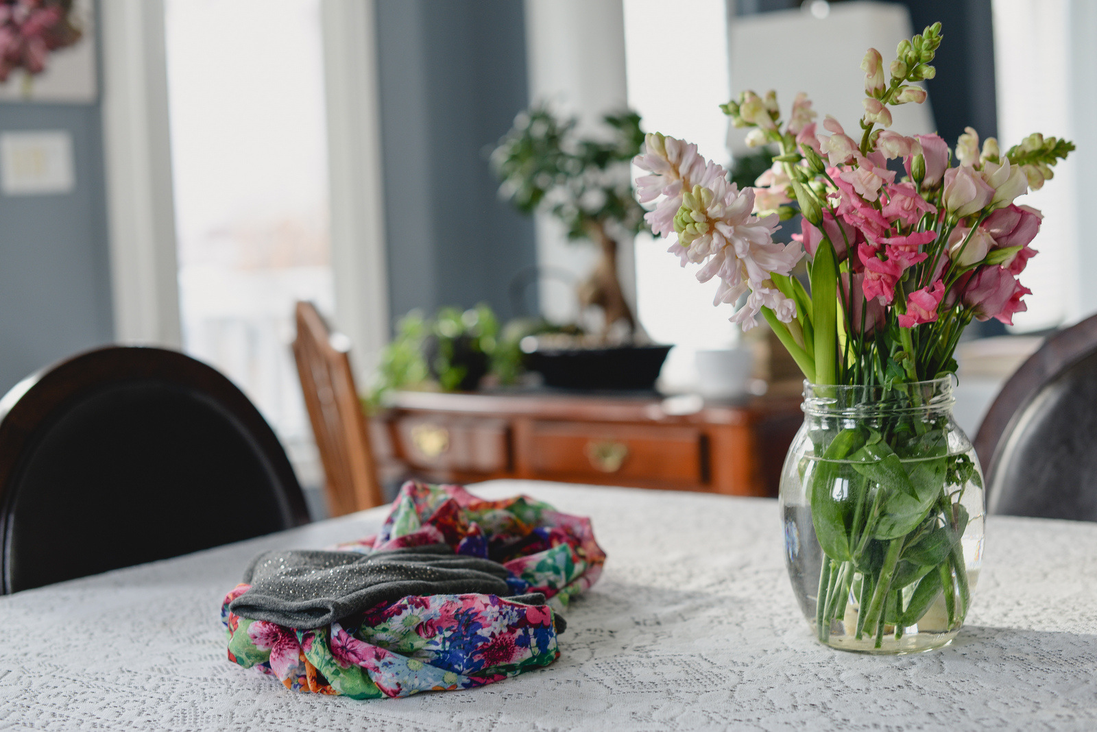 kitchen table with flowers, scarf and gloves