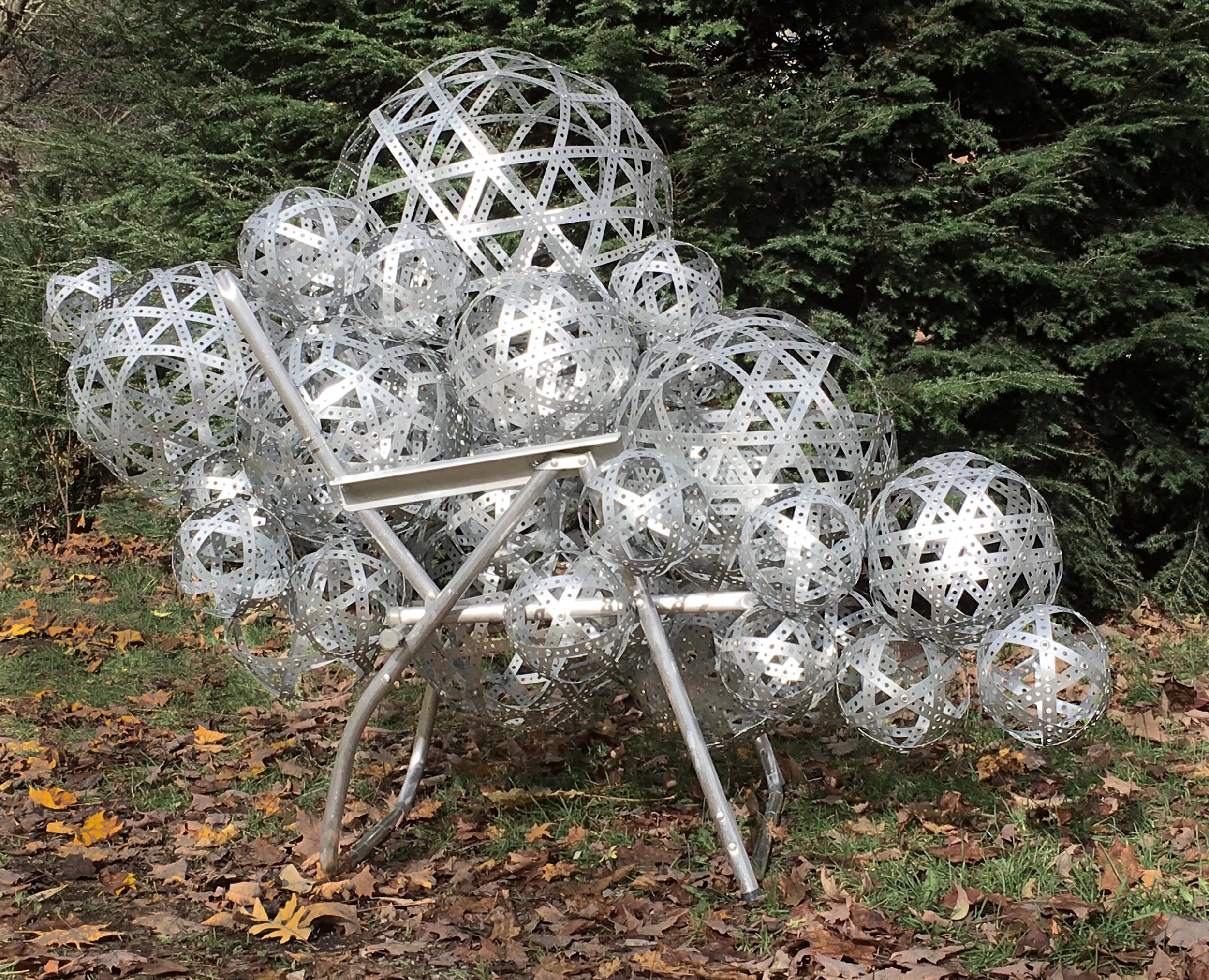 """""""Guest/Host"""" (2018) . side view (fall). 45""""W x 65""""D x 56""""H, Perforated metal strapping, aluminum lawn chair frame, grommets."""
