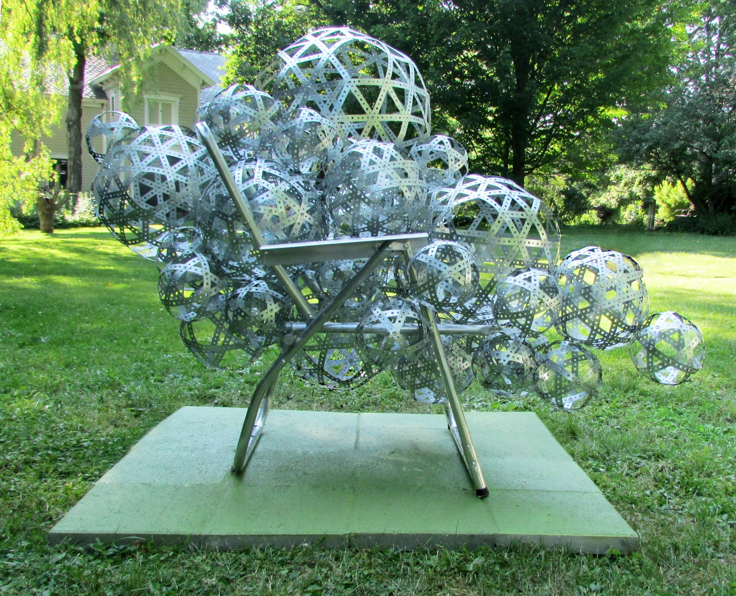 """""""Guest/Host"""" (2018) Left side. 45""""W x 65""""D x 56""""H, Perforated metal strapping, aluminum lawn chair frame, grommets."""
