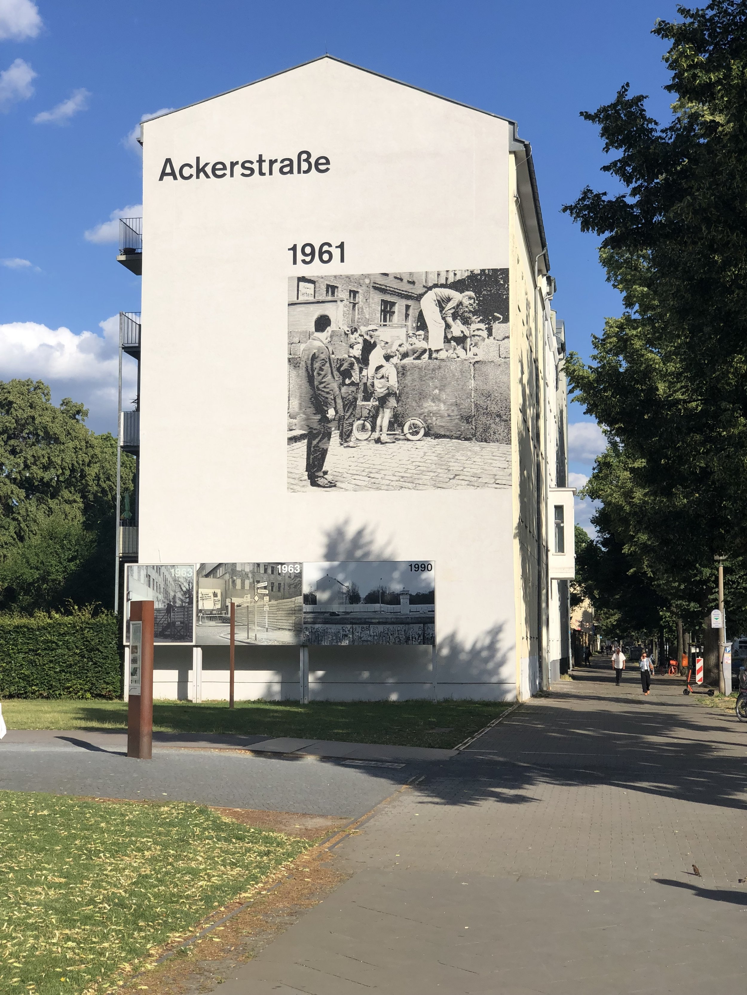 A mural on the side of a building showing the construction of the wall back in 1961.