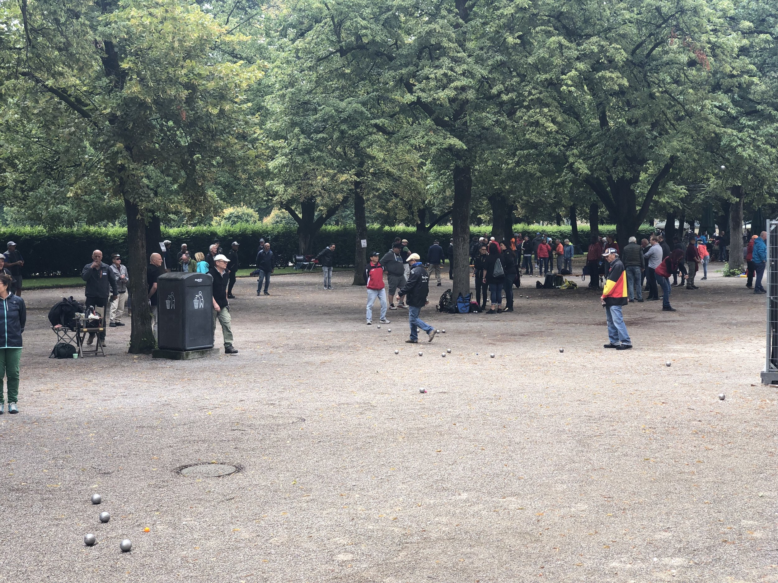 Germans love play a game called petanque, In this area of a city park in Munich there were at least 100 people playing petanque.