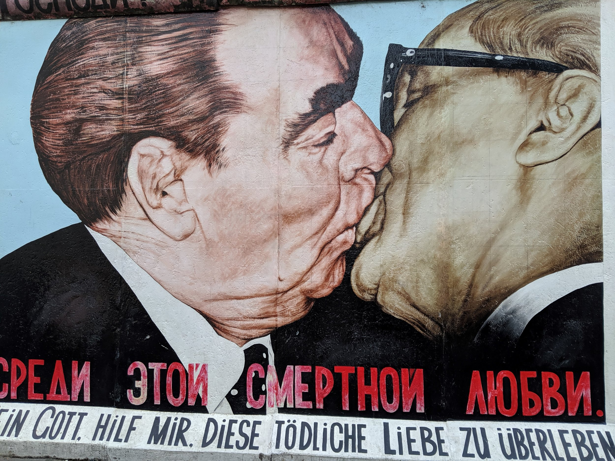 I think his mural depicts the mayors of East and West Berlin after the wall was torn down.