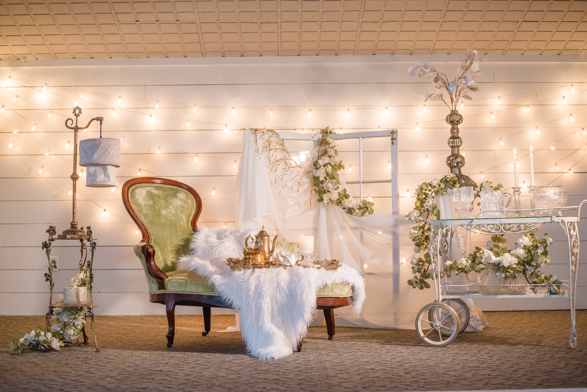 Gwyneth Chaise Lounge ,  Sheffield Tea Cart ,  Gold Floral Plant Stand ,  Wedding Pillars ,  Ornate Flower Stand ,  Brass Tea Pot ,  Gold Mirror Tray ,  Glass Candlesticks ,  Russell Lamp , and  Cream Rose Floral Swag .