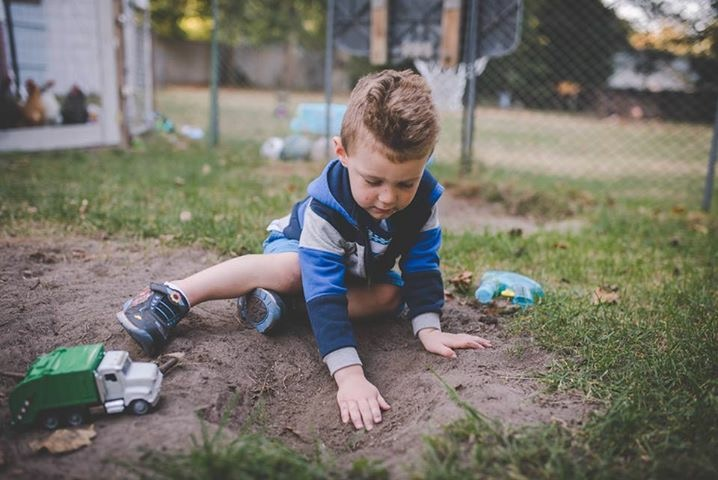 boy playing in dirt with truck