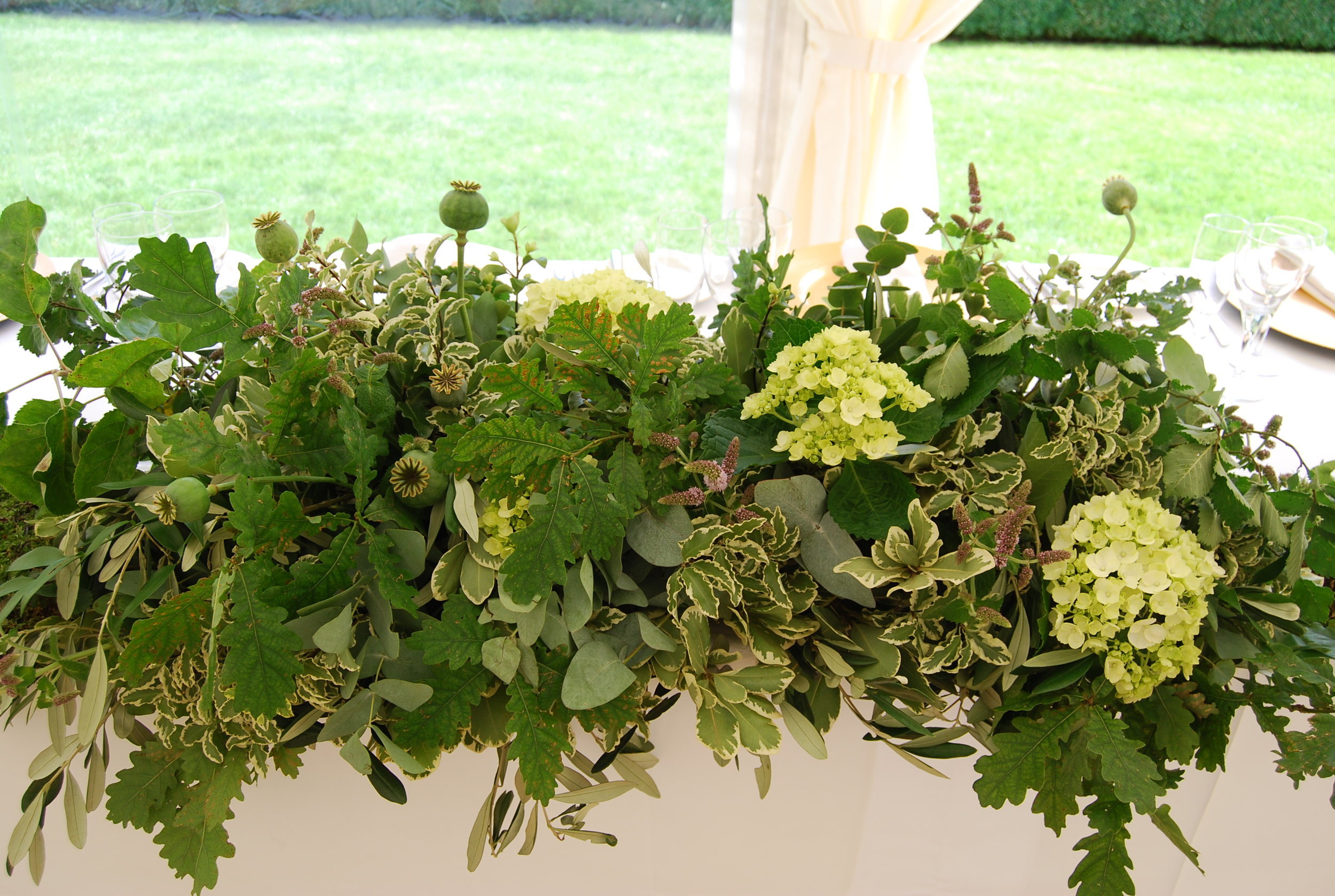 Top table greenery piece full of foliage, hydrangeas and seed heads. Image by  Becky Kerr Photography