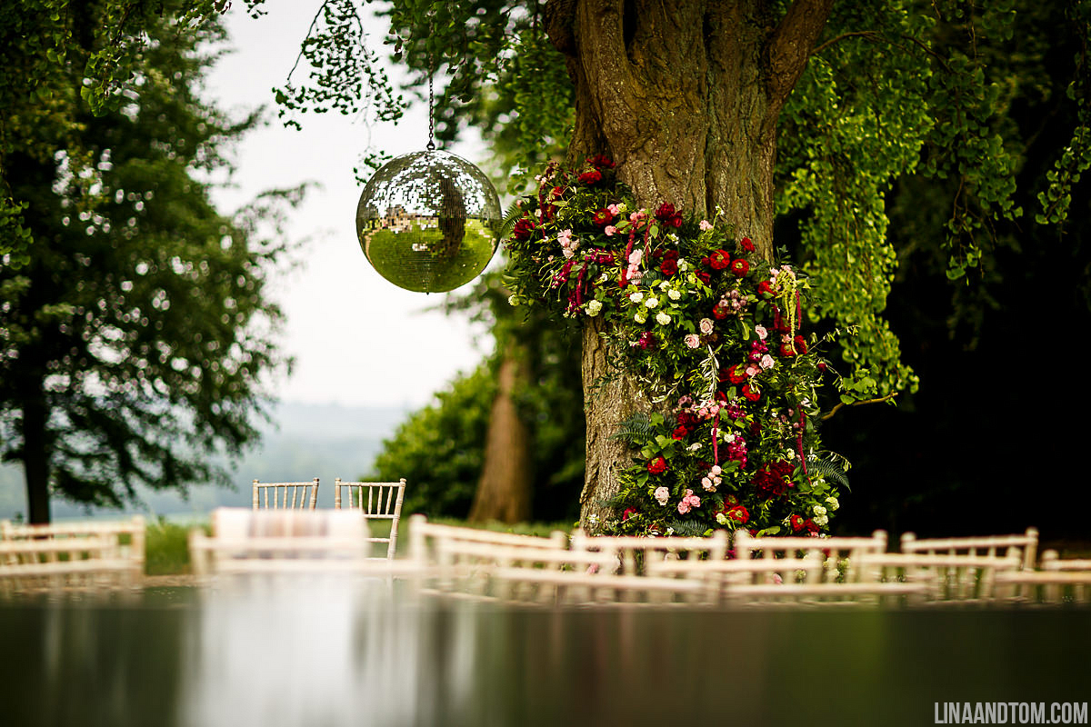 Outdoor ceremony at Aynhoe Park with hanging glitter ball and large floral tree garland by The Flower Story