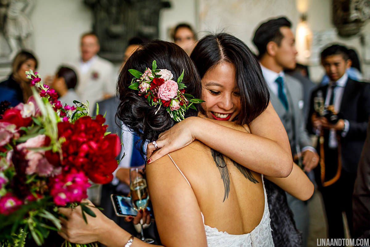 Bride wearing a fresh flower hair comb and carrying a burgundy, pink and blush wedding bouquet full of peonies, roses, snapdragons and jasmine