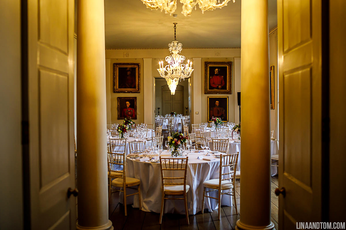 Grand wedding reception room at Aynhoe Park set up for a wedding with floral vases by The Flower Story in the centre of each table