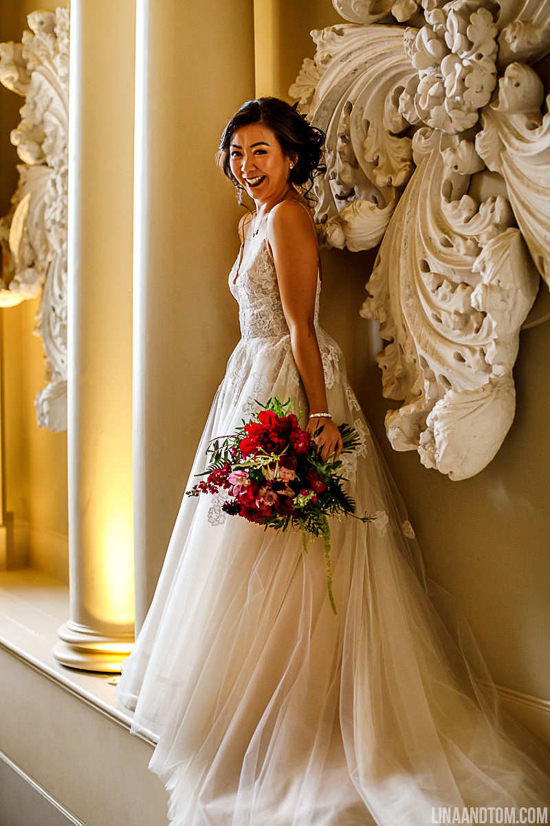 Bride at Aynhoe Park carrying burgandy, pink and blush wedding bouquet by The Flower Story