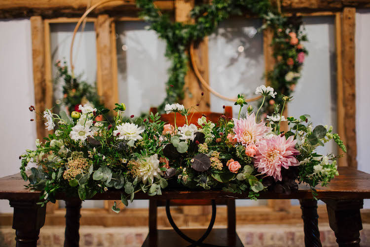 Long and low floral table arrangement in whites and blush with floral hoops hanging behind it.