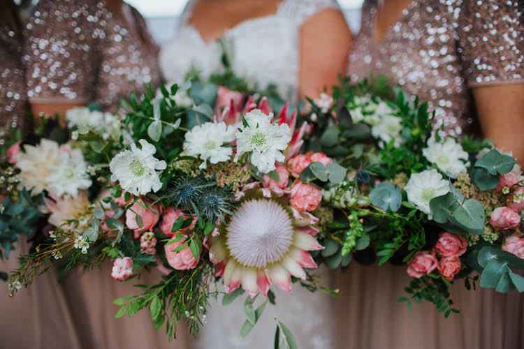 Garden style wedding bouquet full of King proteas, roses and dahlias by The Flower Story