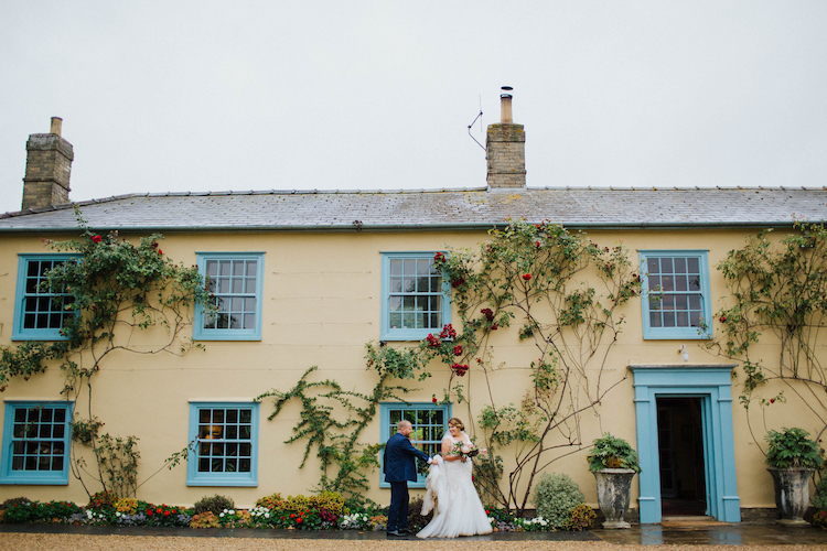 Exterior shot of South Farm main building with bride and groom standing in front