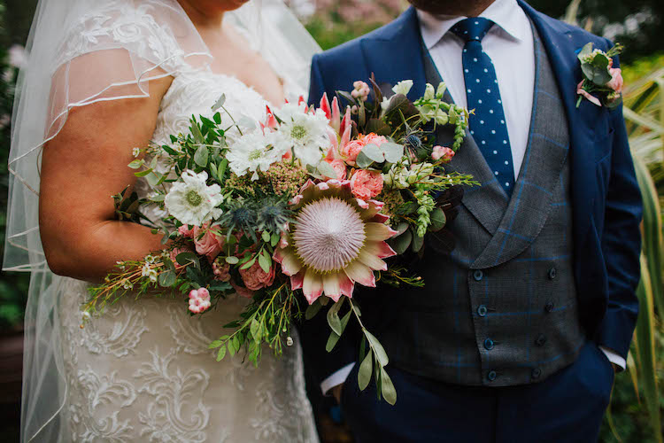 Loose garden style wedding bouquet full of blush King Proteas, roses, scabiosa, berries and snapdragons.