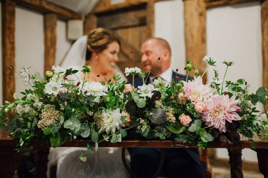 Long and low blush and white floral ceremony table decoration.  Garden style piece full of cafe au lait dahlias, roses, scabiosa and berries