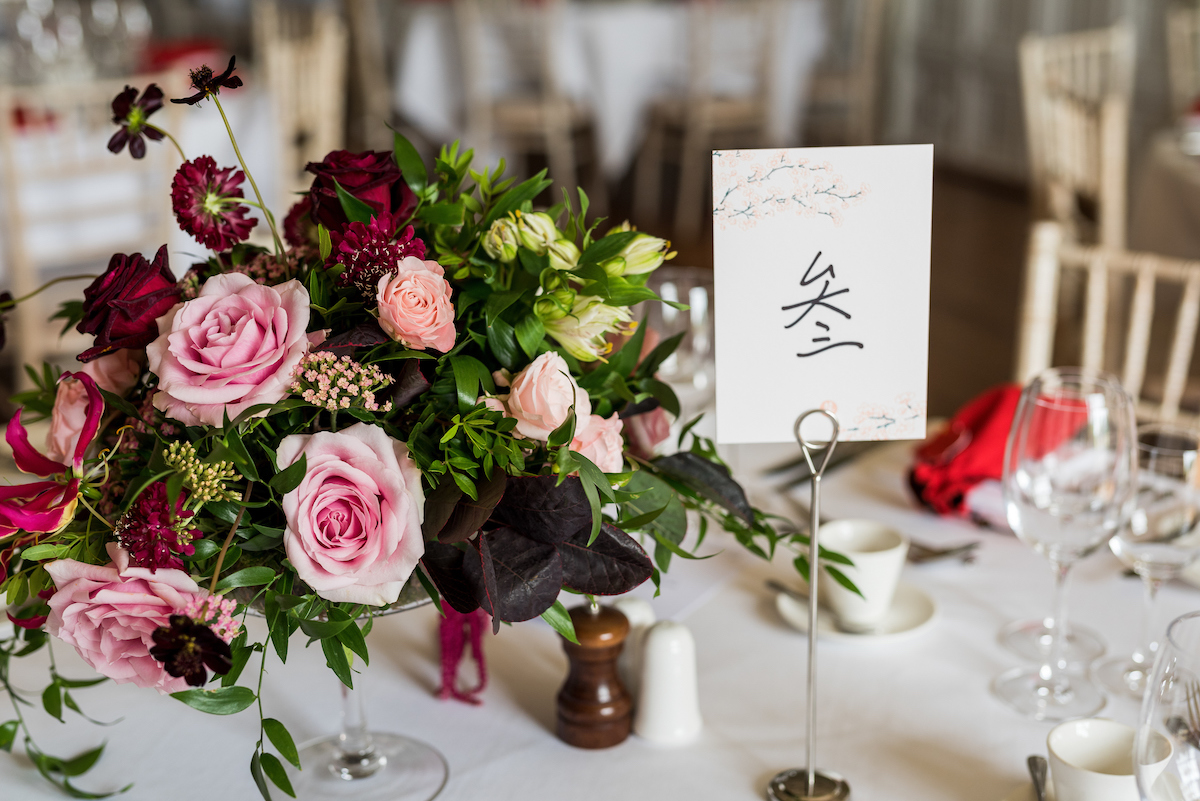 Blush, pink and crimson wedding table centrepiece by The Flower Story