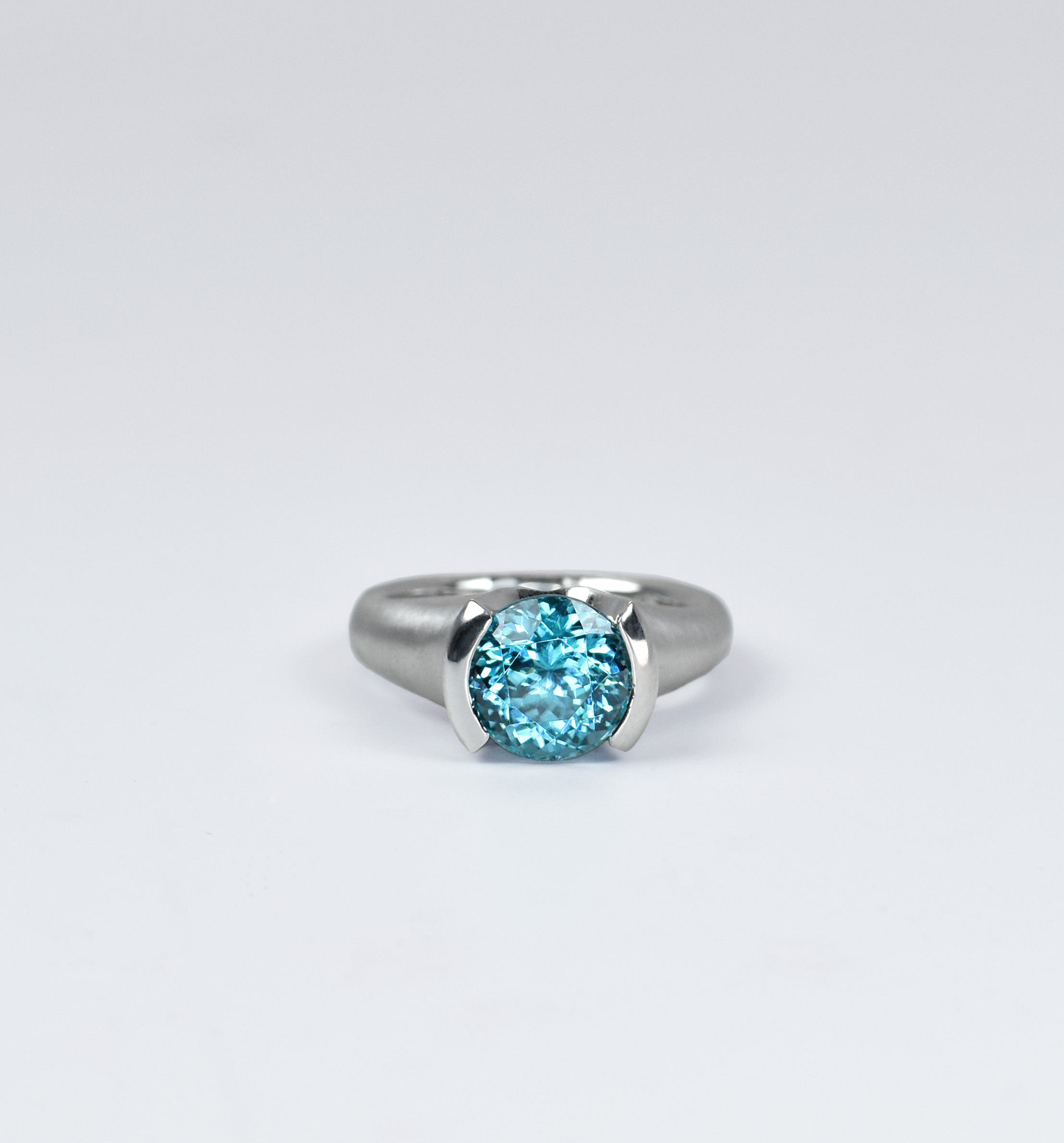 4.42 carat Round Portugese Cut Natural Blue Zircon set in a semi-bezel. Rounded band is a satin finish, while the semi-bezel is polished. 18k white gold.  All hand made, in-house by Dell Taylor