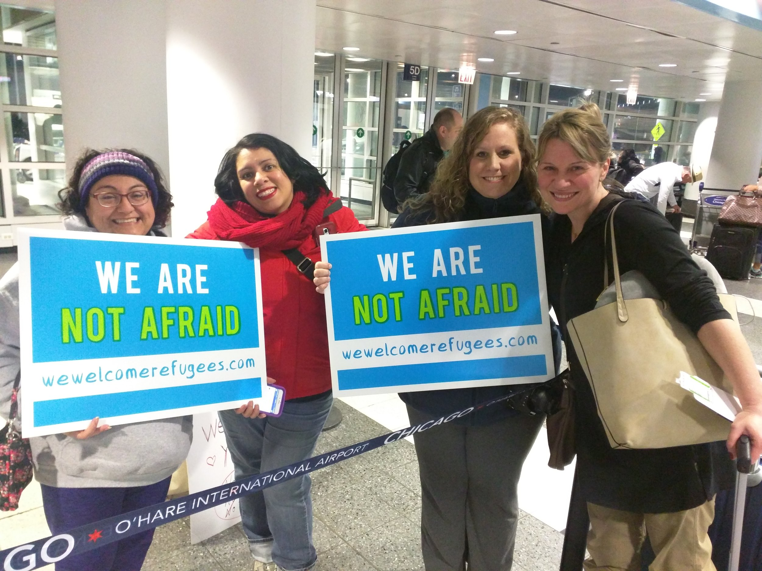 Chicago protesters (from left) Urzula Urzua, Ges Wernher, and Mahra Seward, welcome (right) Sara Ferrara, a UK native, moments after Judge Robart blocked Trumps travel ban.  (Photo/Antonio Garcia)